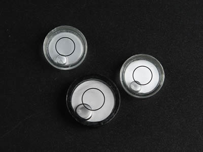 Three glass circular bubble level vials. One is painted with black color.