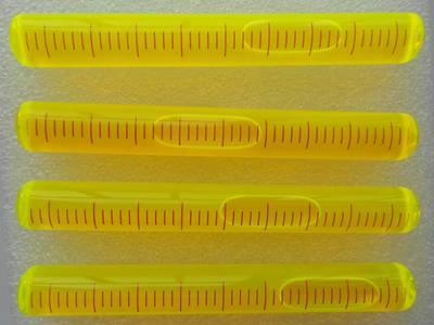 There are four yellow plastic tubular level vials with scale on them.