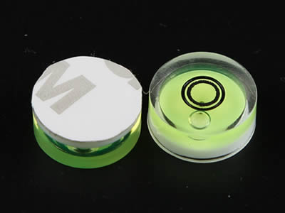 A top view and a bottom view of plastic bubble level vial with adhesive.
